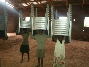 Girls in Malawi carry chairs