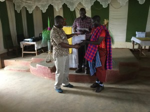 Frank and Pastor David present a certificate to a Masai participant