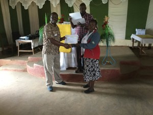 Frank awards a certificate to a Masai woman.