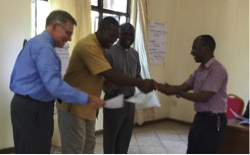 Wayne, Frank Tweheyo and Domnic Misolo (L to R) present a completion certificate to Eliya Musa, who also provided English to Swahili translation for the seminar.