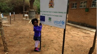 """While on a tour of Rochelle's """"Demonstration Project,"""" the Holm's daughter Mphatso explained the particulars of Rochelle's work as the Manager of the Mzuzu University Centre of Excellence in Water and Sanitation where she leads the effort to network regional water and sanitation work and also the training of professionals through Mzuzu University."""
